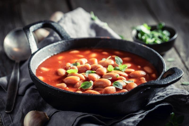 Haricots cuits au four chauds avec la sauce tomate et les herbes fraîches photographie stock libre de droits