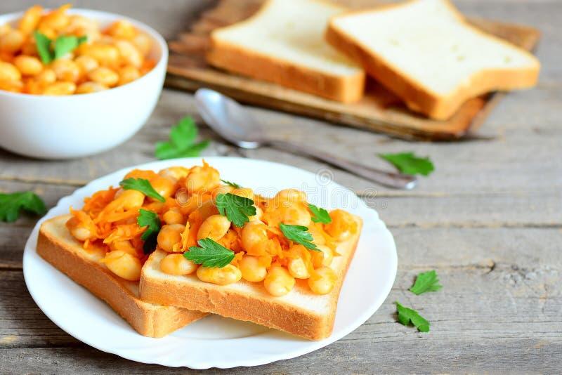 Haricots cuits au four sur le pain Les haricots ont fait cuire au four avec les légumes dans une cuvette, tranches de pain sur un images libres de droits