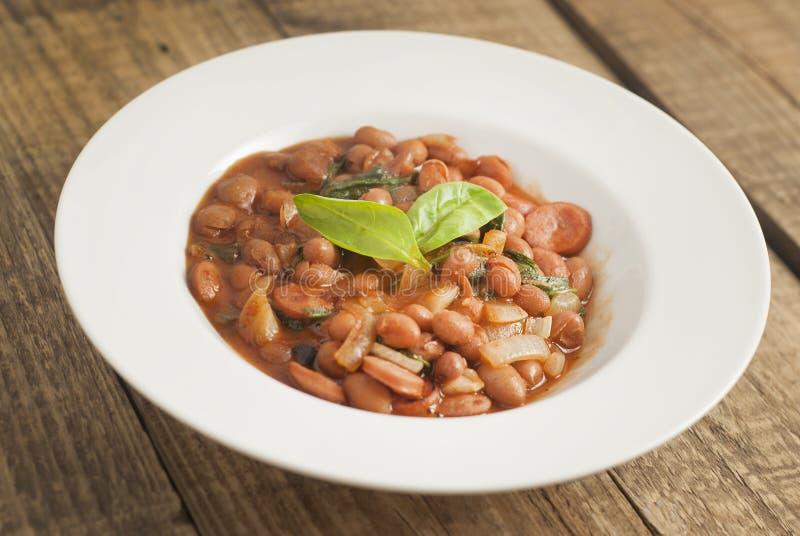 Haricots rouges cuits en sauce tomate avec les épinards et l'oignon, plat rond blanc, fond en bois, vue supérieure photos libres de droits