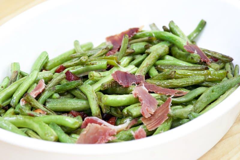 Haricots verts frits avec du jambon images stock