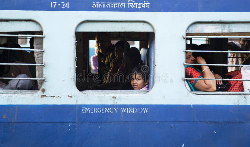 HARIDWAR, INDIA - April 04, 2014 - Indian girl in the train looking out the window and smiling. stock photography