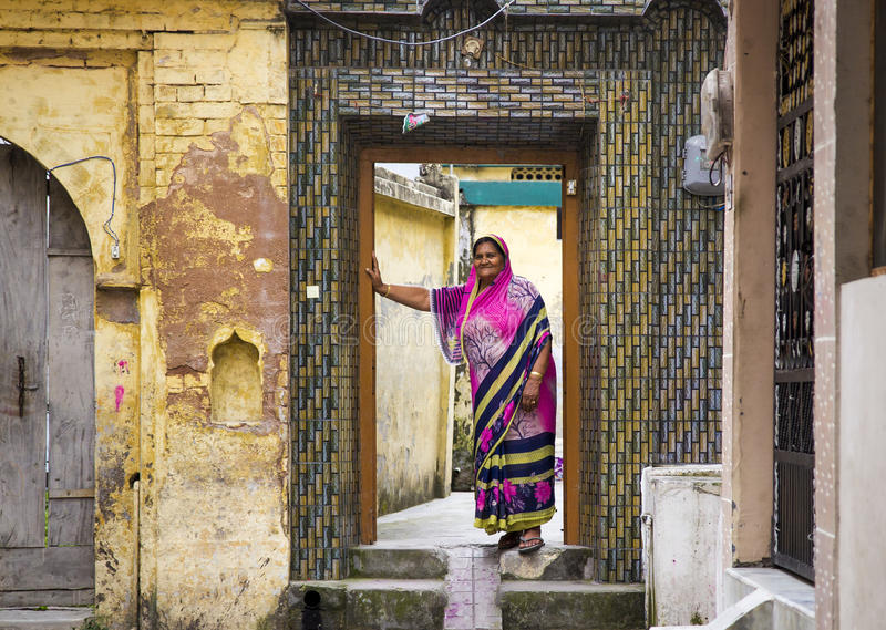 HARIDWAR, INDIA - MAART 23, 2014: Indische vrouw die kleurrijke Sari in de deuropening dragen royalty-vrije stock fotografie