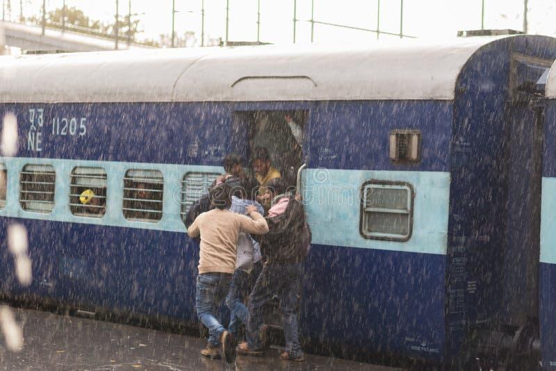 Haridwar, India - March 11, 2017: Crowd boarding train in Haridwar railway station under heavy monsoon rain. Young boys fighting t stock photos