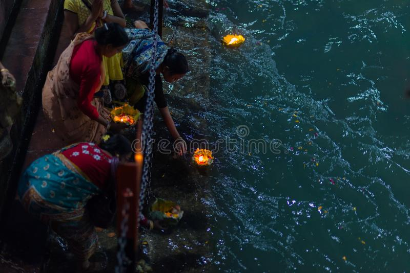 Haridwar, India - March 20, 2017: Holy ghats at Haridwar, India, sacred town for Hindu religion. Pilgrims offering floating flowe. Rs and burning candles to the royalty free stock images