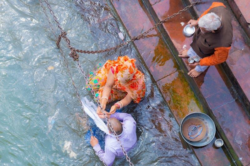 Haridwar, India - 11 marzo 2017: gente non identificata che bagna e che prende le abluzioni nel Gange ai ghats santi in Haridw fotografia stock