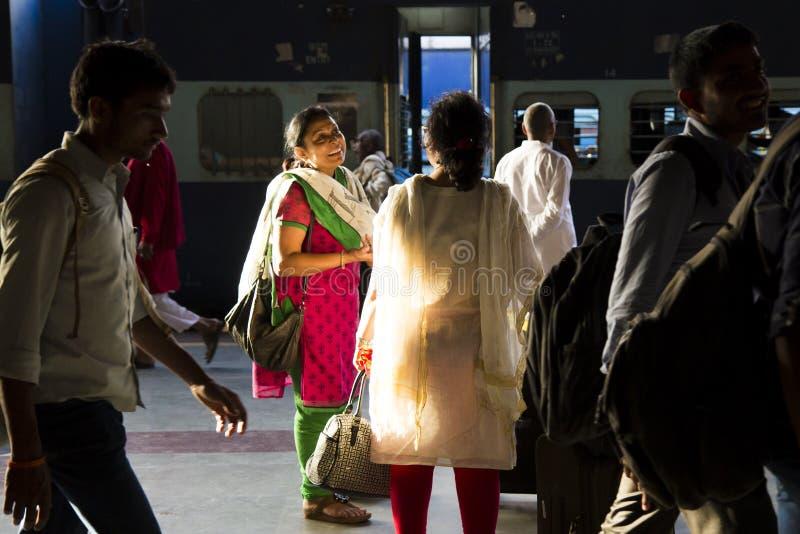 HARIDWAR, INDIEN - 4. April 2014 - Leute am Bahnhof, indische Frau im Sonnenlicht, die Sari lächelnd und sprechend trägt lizenzfreies stockfoto