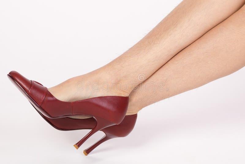 Harige benen van een vrouw in rode schoenen stock fotografie