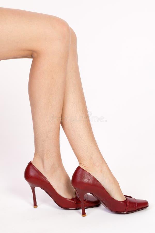 Harige benen van een vrouw in rode schoenen stock foto's