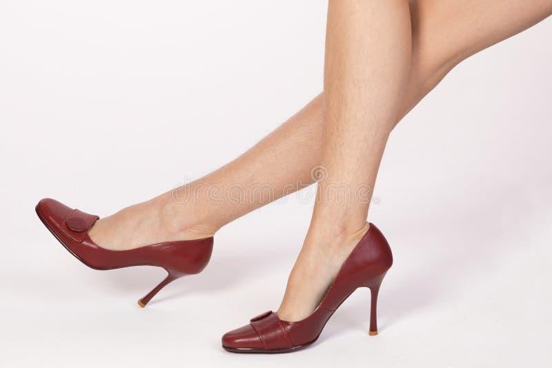Harige benen van een vrouw in rode schoenen royalty-vrije stock foto