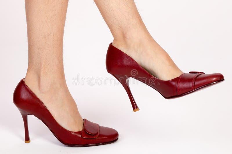 Harige benen van een vrouw in rode schoenen royalty-vrije stock fotografie