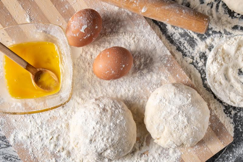 Harina blanca con los huevos, la mantequilla y la pasta en un tablero de cocinar imagen de archivo libre de regalías
