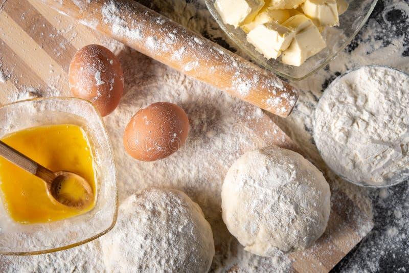 Harina blanca con los huevos, la mantequilla y la pasta en un tablero de cocinar foto de archivo