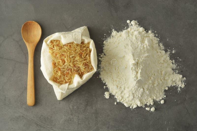 Harina de arroz y arroz sobre fondo oscuro El gluten libera la harina imagenes de archivo