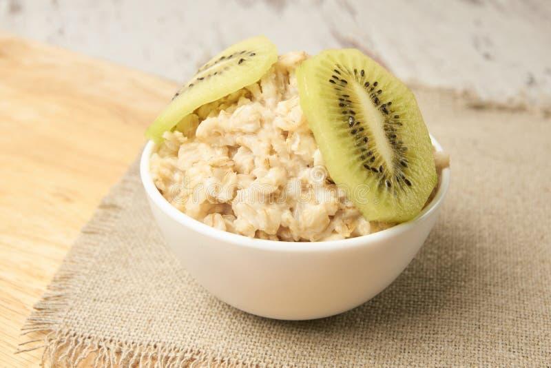 Harina de avena con el kiwi Fondo útil del neutral del desayuno fotos de archivo