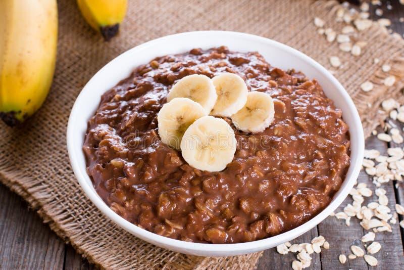 Harina de avena del chocolate para el desayuno con las rebanadas de un plátano maduro en un cuenco blanco en un fondo de madera e fotos de archivo