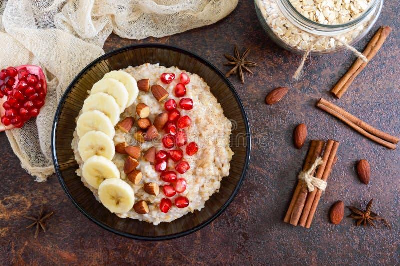 Harina de avena deliciosa y sana con el plátano, las semillas de la granada, la almendra y el canela fotos de archivo