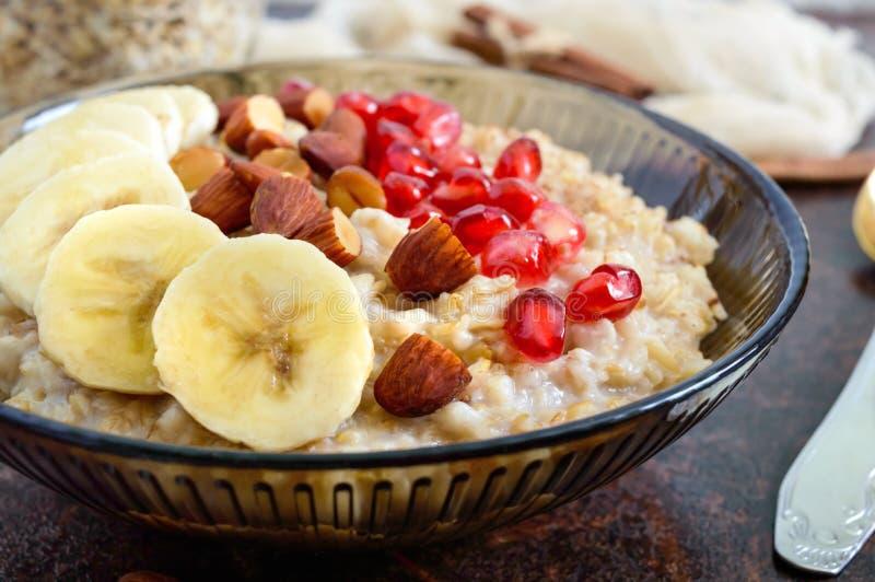 Harina de avena deliciosa y sana con el plátano, las semillas de la granada, la almendra y el canela imagen de archivo libre de regalías