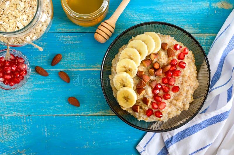 Harina de avena deliciosa y sana con el plátano, las semillas de la granada, la almendra y el canela fotografía de archivo