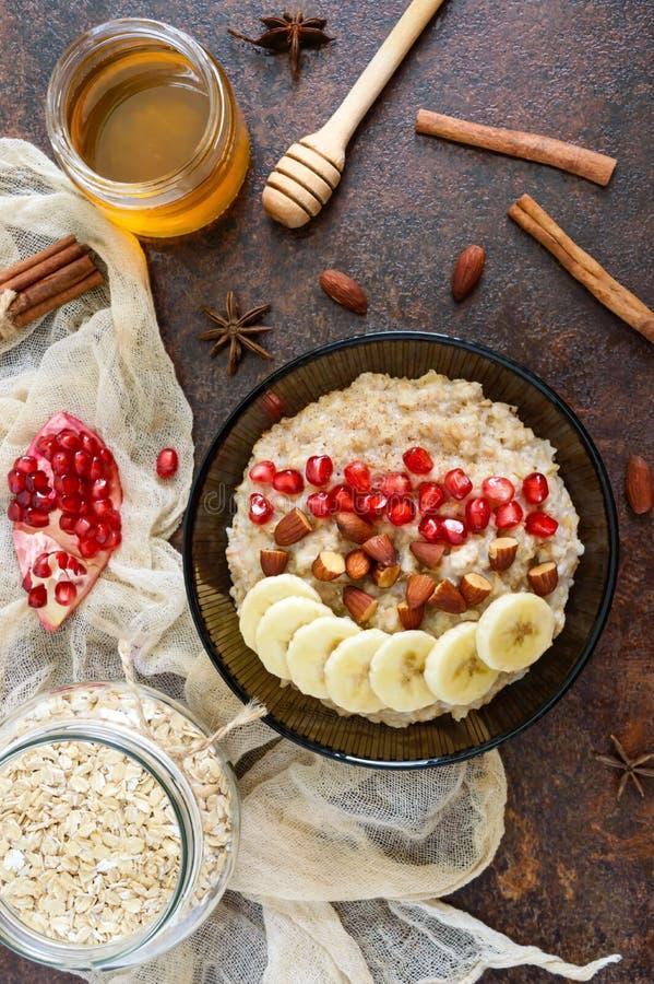 Harina de avena deliciosa y sana con el plátano, las semillas de la granada, la almendra y el canela foto de archivo