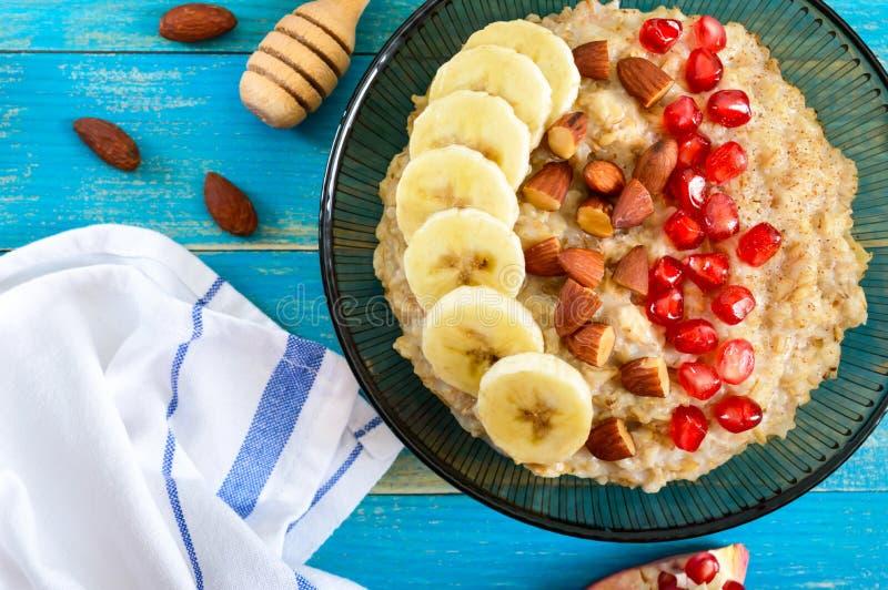 Harina de avena deliciosa y sana con el plátano, las semillas de la granada, la almendra y el canela imagen de archivo