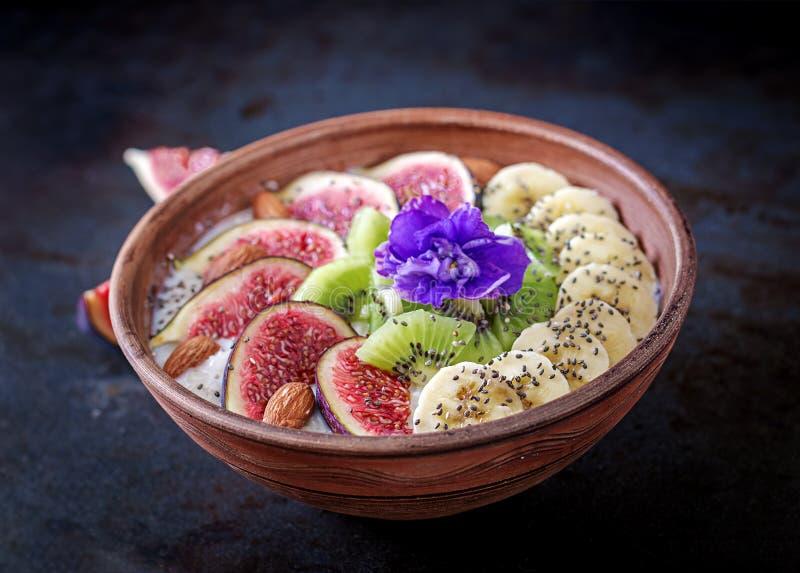 Harina de avena deliciosa y sana con las semillas de los higos, del kiwi, del plátano, de la almendra y del chia fotos de archivo libres de regalías