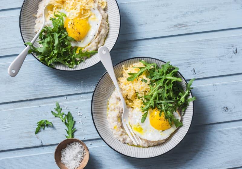 Harina de avena sabrosa del queso con el huevo frito y el arugula en un fondo azul, visión superior Desayuno equilibrado sano fotografía de archivo libre de regalías