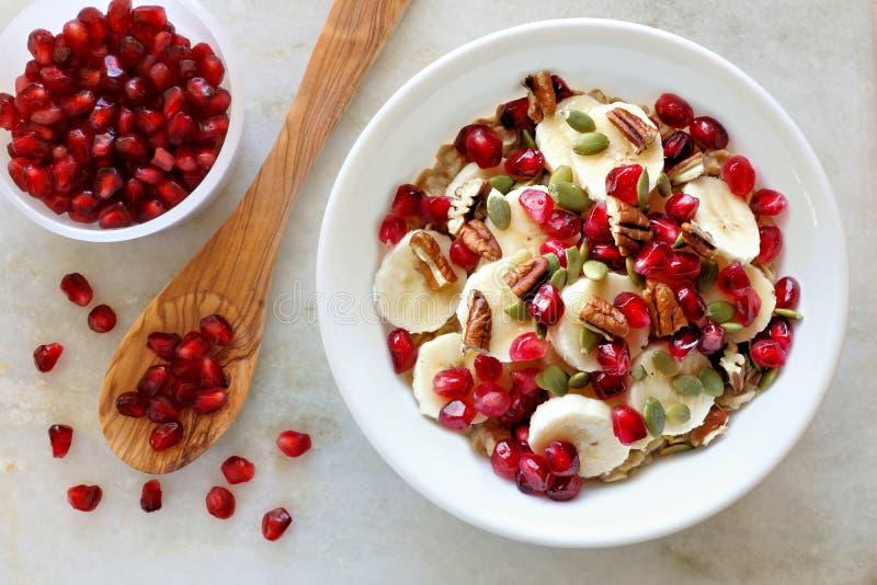 Harina de avena sana del desayuno con la granada, los plátanos, las semillas y las nueces foto de archivo libre de regalías