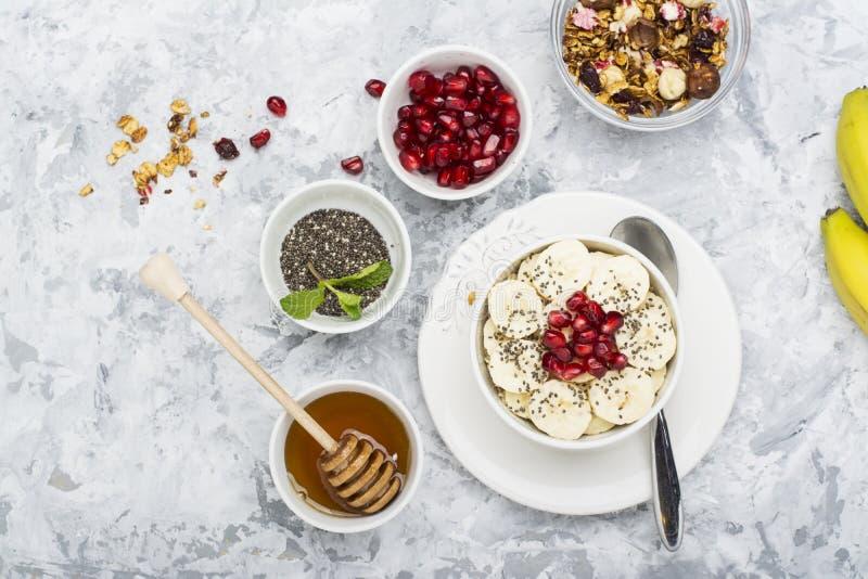 Harina de avena sana del desayuno con la granada, los plátanos, las semillas y las nueces, escena de arriba en el mármol blanco V foto de archivo