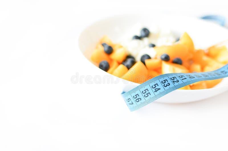 Harina de avena y fruta con cierre de la cinta métrica para arriba en un fondo blanco Foco selectivo Adiete el concepto Sano y fi imagen de archivo libre de regalías