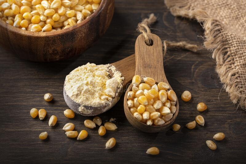 Harina de maíz en una cuchara de madera fotos de archivo