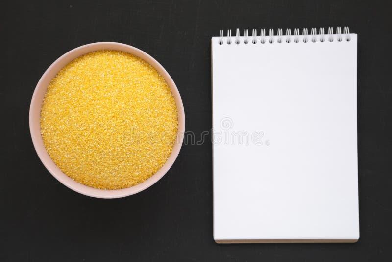Harina de maíz orgánica seca de Masarepa en un cuenco rosado, libreta en blanco sobre el fondo negro, visión superior Endecha pla imágenes de archivo libres de regalías