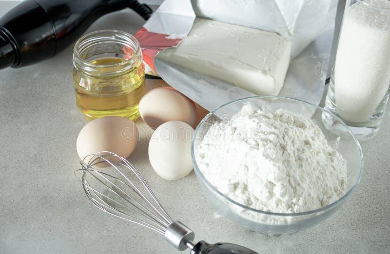 Harina y azúcar en un envase de cristal, huevos y mantequilla en la tabla foto de archivo