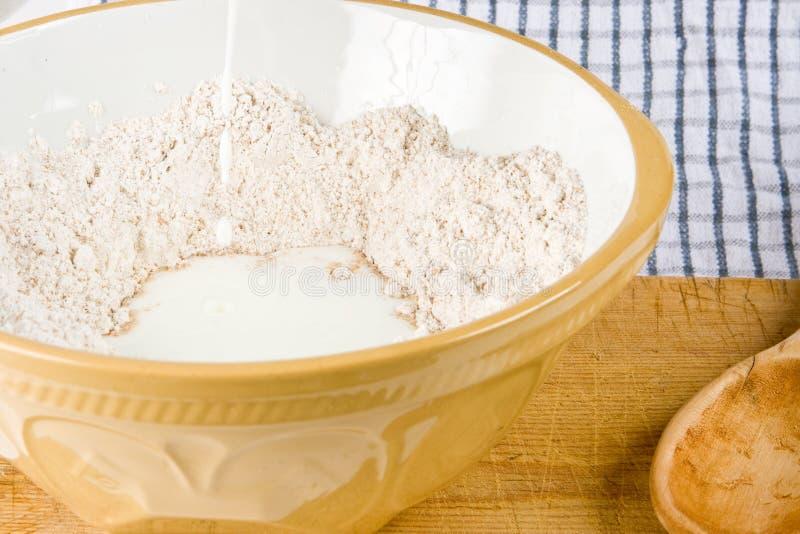 Harina y leche en un tazón de fuente imagen de archivo