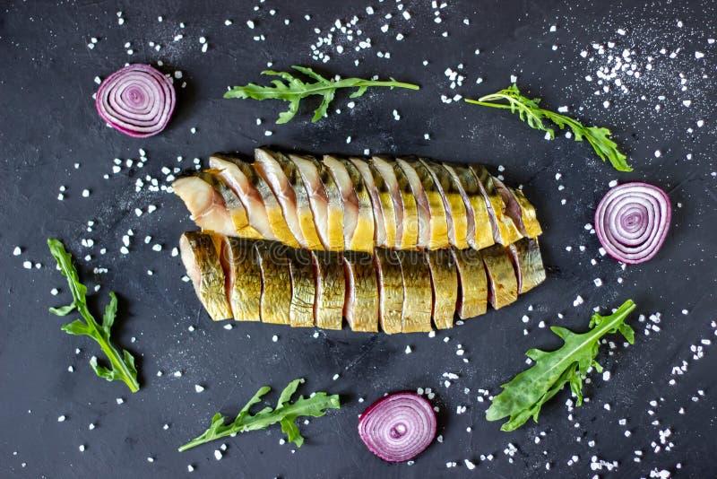 Haringen en makreel op een donkere achtergrond met uien en arugula royalty-vrije stock foto's