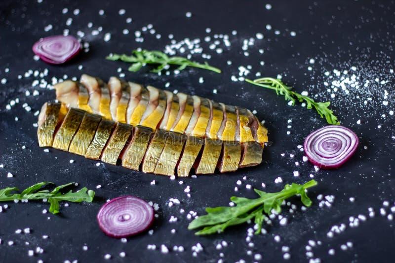 Haringen en makreel op een donkere achtergrond met uien en arugula royalty-vrije stock afbeeldingen