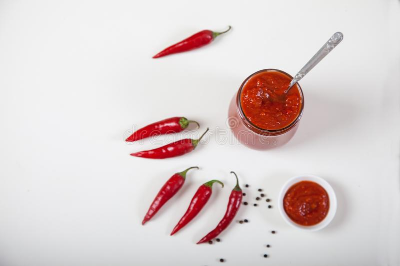 Harissa in a glass jar with a spoon, a small plate with harissa and red hot pepper on a white background. copy spaes. royalty free stock photos