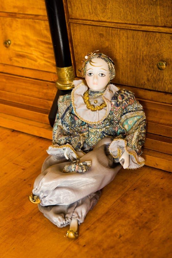 Harlekindocka på ett antikt körsbärsrött wood skrivbord arkivfoton