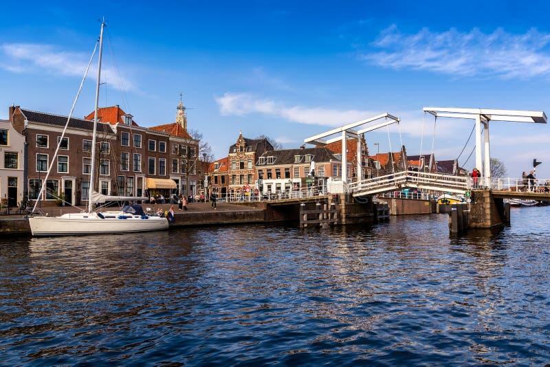 HARLEM, DIE NIEDERLANDE - 14. APRIL 2018: Spaarne-Fluss mit Booten, berühmter touristischer Brücke und Häusern Markstein Graveste lizenzfreie stockfotos