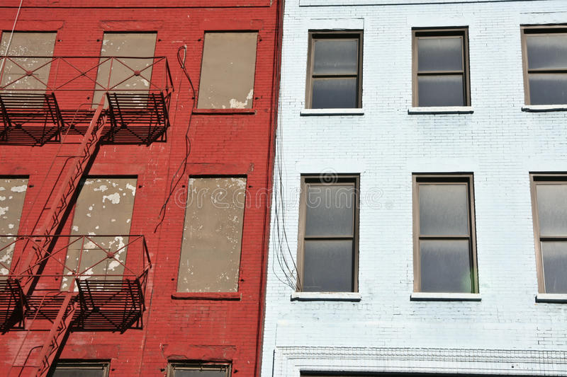 Harlem fire escape. Three colorful, red, brown and white, apartment buildings facades with emergency escapes. Typical New York City rental complexes with fire royalty free stock images