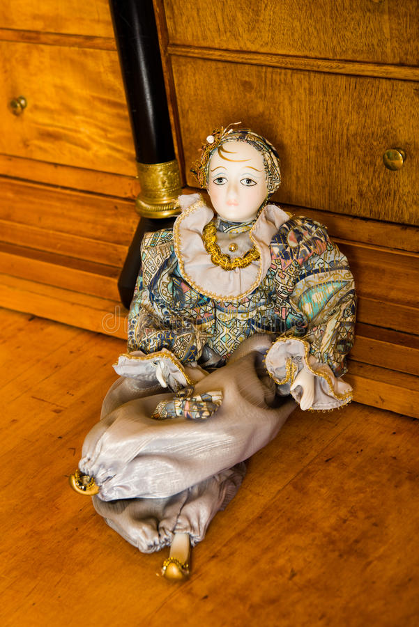 Harlequin doll on an antique cherry wood desk stock photos
