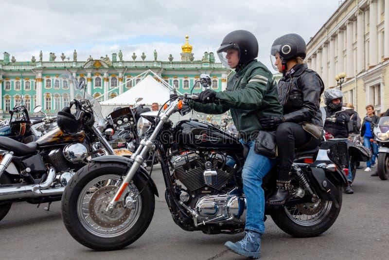 Harley-Davidson Motorcycle Festival - una coppia di motociclisti nei giri dei caschi lungo il quadrato del palazzo su un motocicl fotografia stock libera da diritti