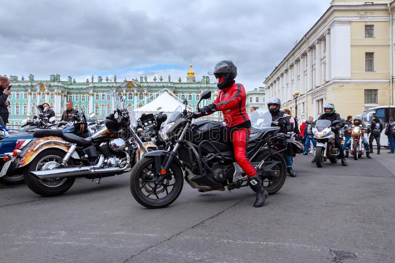 Harley-Davidson Motorcycle Festival - Woman biker in a helmet and a red leather jacket and trousers rides a motorbike on Palace Sq stock photos