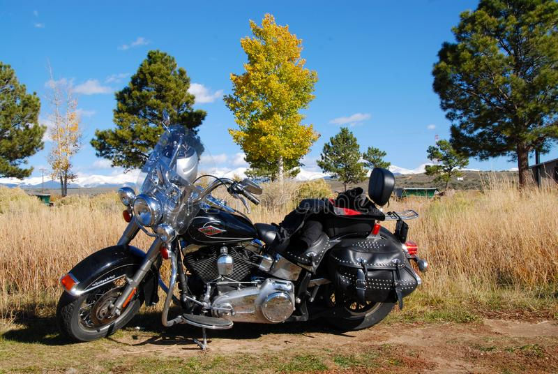 Harley Davidson motorcycle with snow covered mountains in fall royalty free stock images