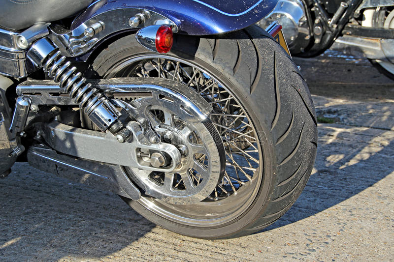 Harley davidson rear chunky wheel. Photo of a chunky rear wheel belonging to a harley davidson motorbike with lots of chrome stock image