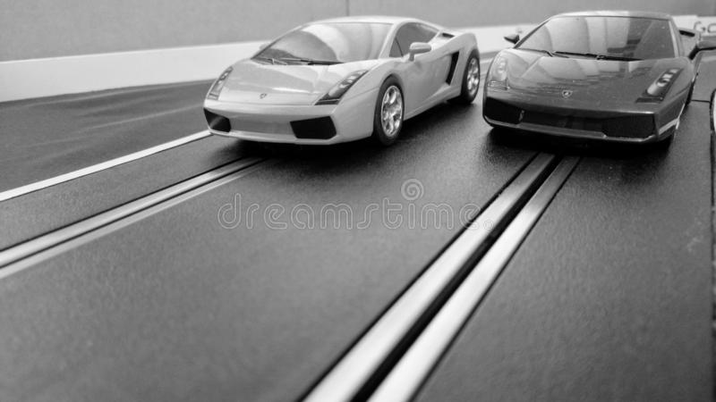 Harlow, England - March 06 2019: Slot cars racing on a slot car track, black and white for a retro look royalty free stock photo