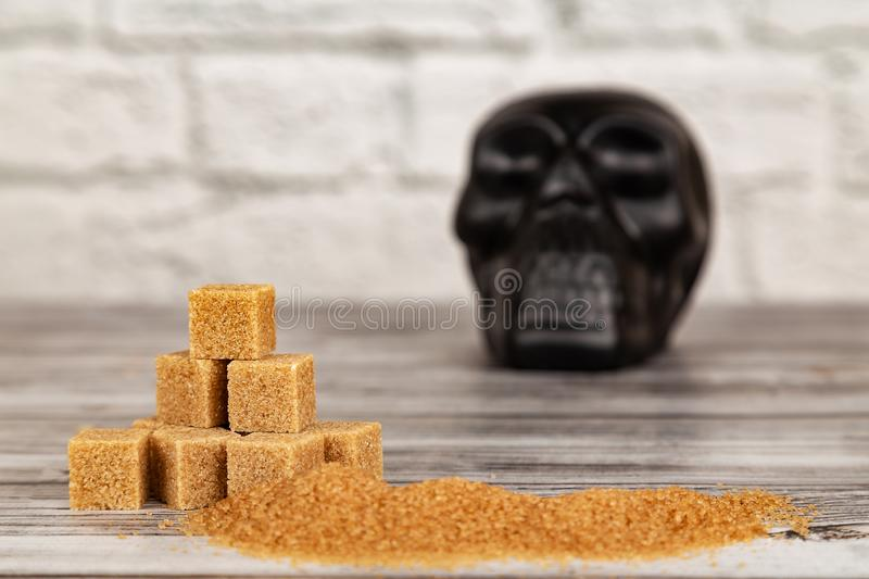 Harm of sugar concept. Cubes of sugar and black skull figure royalty free stock photo