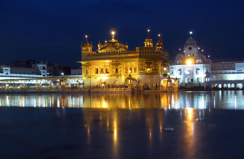 Harmandir Sahib, Amritsar, night view. People in a line to a holy book Harmandir Sahib - Golden Temple, in Amritsar, India. The holy place of worship of the royalty free stock photo