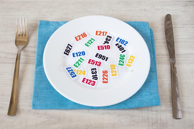 Harmful food additives. There are several tables with the code E-additives on the plate stock photo