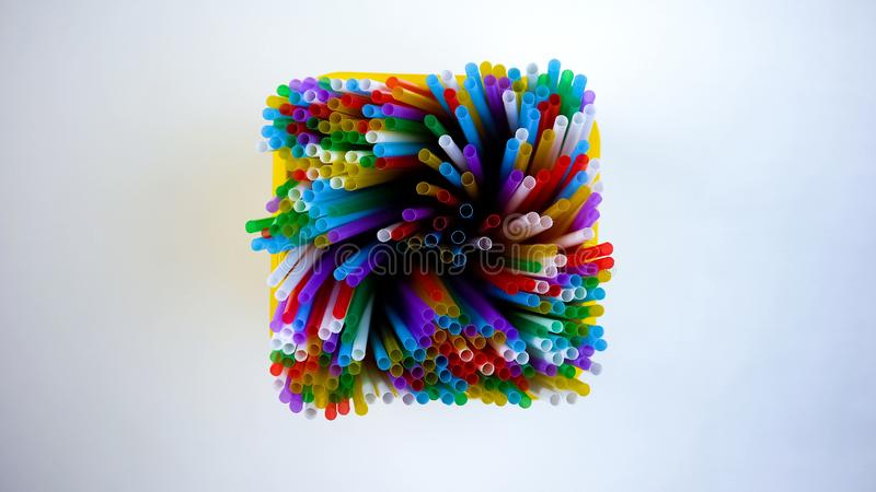 Harmful usage of colorful plastic straws in yellow box, environmental pollution stock photos