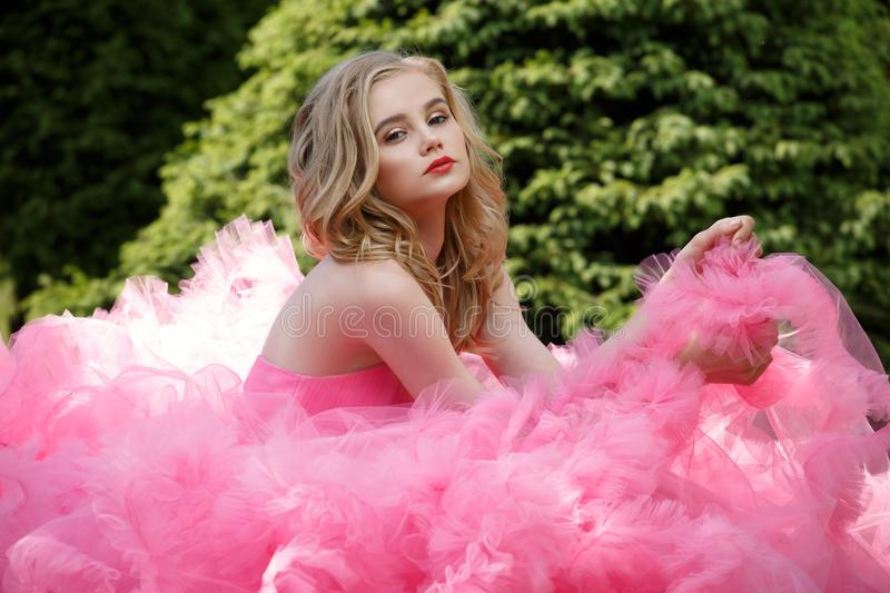 Harming young woman with blonde locks and makeup wearing pink evening dress with fluffy skirt is posing outdoors near the bush. Beautiful, charming young woman royalty free stock photography